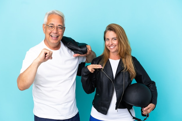 Coppia di motociclisti di mezza età con un casco da motociclista isolato su sfondo blu orgoglioso e soddisfatto di sé nell'amore te stesso concept