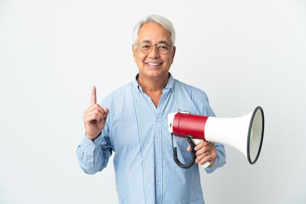 Uomo brasiliano di mezza età isolato su sfondo bianco che tiene in mano un megafono e punta verso l'alto una grande idea