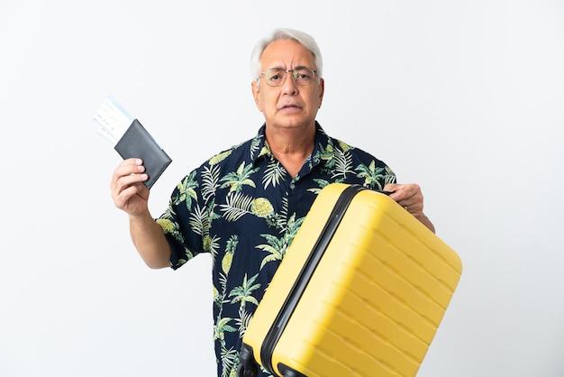 Uomo brasiliano di mezza età isolato su sfondo bianco infelice in vacanza con la valigia e il passaporto