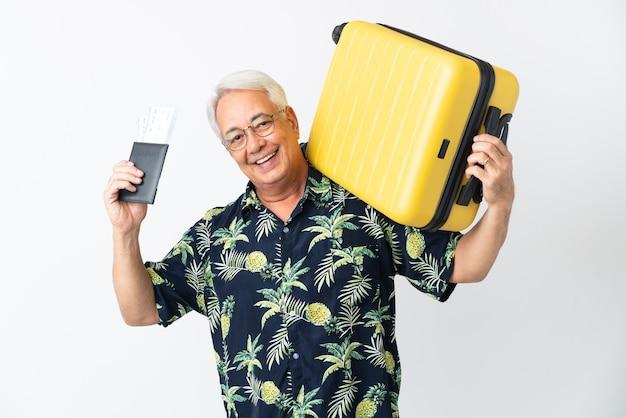 Uomo brasiliano di mezza età isolato su priorità bassa bianca in vacanza con la valigia e il passaporto