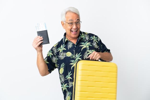 Uomo brasiliano di mezza età isolato su sfondo bianco in vacanza con valigia e passaporto