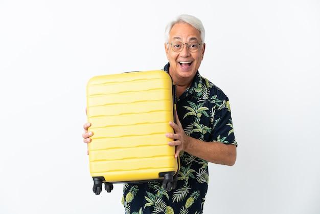 Uomo brasiliano di mezza età isolato su sfondo bianco in vacanza con valigia da viaggio e sorpreso