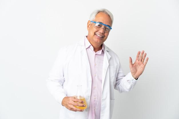 Uomo scientifico brasiliano di mezza età scientifico isolato su sfondo bianco salutando con la mano con espressione felice