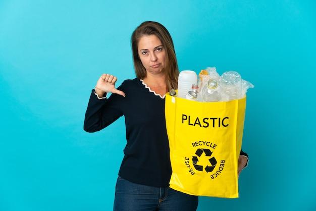 Donna brasiliana di mezza età che tiene un sacchetto pieno di bottiglie di plastica da riciclare