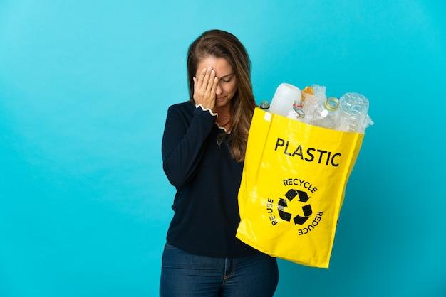 Donna brasiliana di mezza età che tiene una borsa piena di bottiglie di plastica