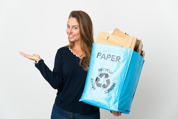 Donna brasiliana di mezza età che tiene una borsa per il riciclaggio piena di carta da riciclare su mani isolate che si estendono di lato per invitare a venire