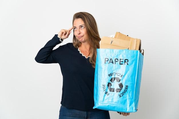 Donna brasiliana di mezza età che tiene un sacchetto di riciclaggio pieno di carta da riciclare sopra isolato avendo dubbi e pensiero