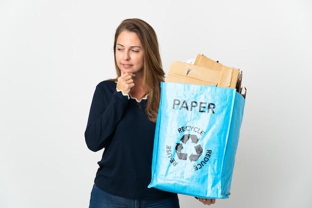Donna brasiliana di mezza età che tiene un sacchetto di riciclaggio pieno di carta da riciclare sopra isolato che osserva al lato e che sorride
