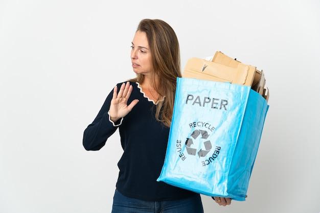 Donna brasiliana di mezza età che tiene un sacchetto di riciclaggio pieno di carta da riciclare sopra isolato facendo gesto di arresto e deluso