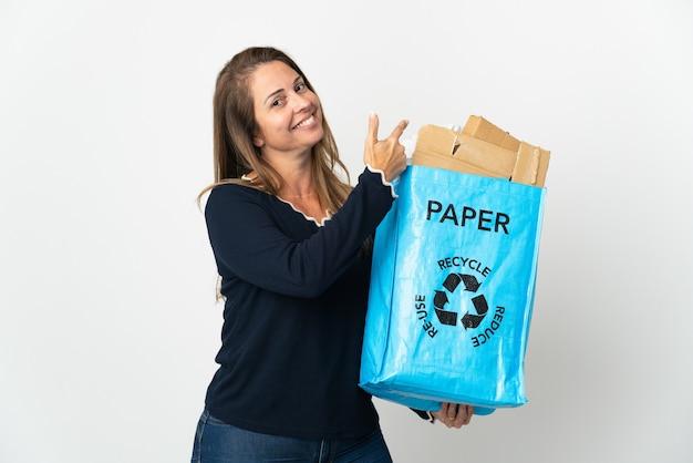 Donna brasiliana di mezza età che tiene un sacchetto di riciclaggio pieno di carta da riciclare sopra isolato che indica indietro