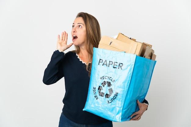 Donna brasiliana di mezza età che tiene un sacchetto di riciclaggio pieno di carta da riciclare