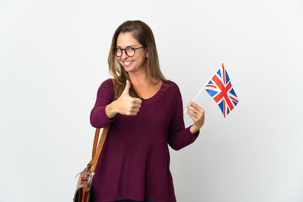 Donna brasiliana di mezza età che tiene una bandiera del regno unito isolata su sfondo bianco con il pollice in alto perché è successo qualcosa di buono