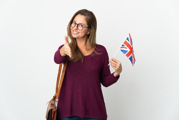 Donna brasiliana di mezza età che tiene una bandiera del regno unito isolata su bianco che agitano le mani per chiudere un buon affare