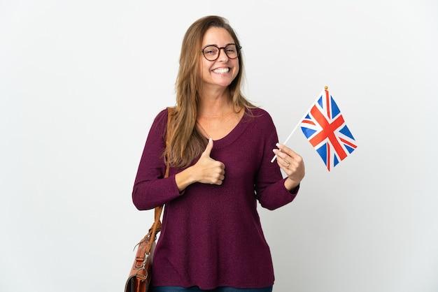 Donna brasiliana di mezza età che tiene una bandiera del regno unito isolata sul muro bianco che dà un pollice in alto gesto