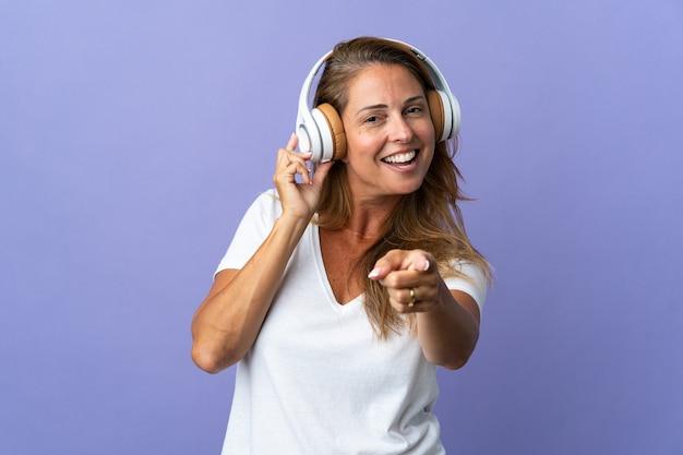 Donna brasiliana di mezza età isolata sulla musica d'ascolto viola e che indica la parte anteriore