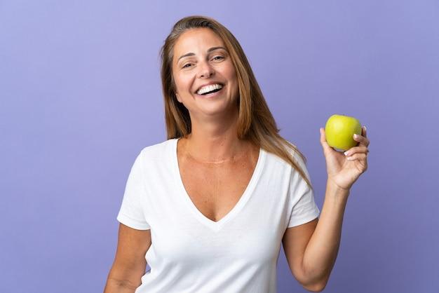 Donna brasiliana di mezza età isolata sulla porpora con una mela e felice