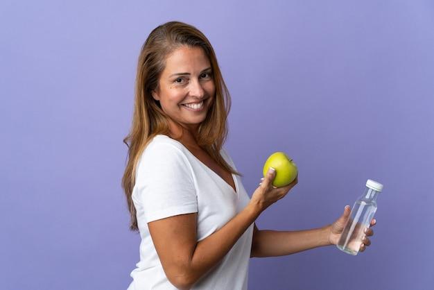 Donna brasiliana di mezza età isolata su viola con una mela e con una bottiglia d'acqua