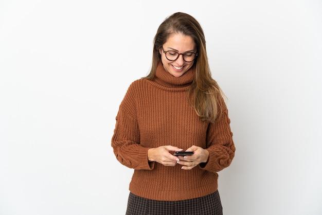 Donna brasiliana di mezza età isolata sul muro bianco che invia un messaggio con il cellulare