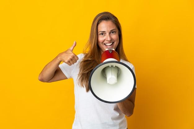 Donna brasiliana di mezza età isolata sulla parete gialla che grida tramite un megafono per annunciare qualcosa e con il pollice in su