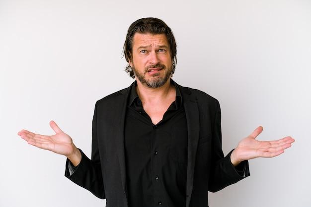 Uomo olandese di affari di mezza età isolato su sfondo bianco confuso e dubbioso scrollare le spalle per tenere uno spazio di copia.