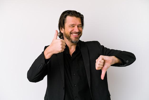 L'uomo olandese di affari di mezza età isolato su priorità bassa bianca tiene le mani sotto il mento, sta guardando felicemente da parte.