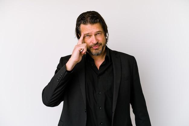 Uomo olandese di affari di mezza età isolato su sfondo bianco che punta il tempio con il dito, pensando, concentrato su un compito.
