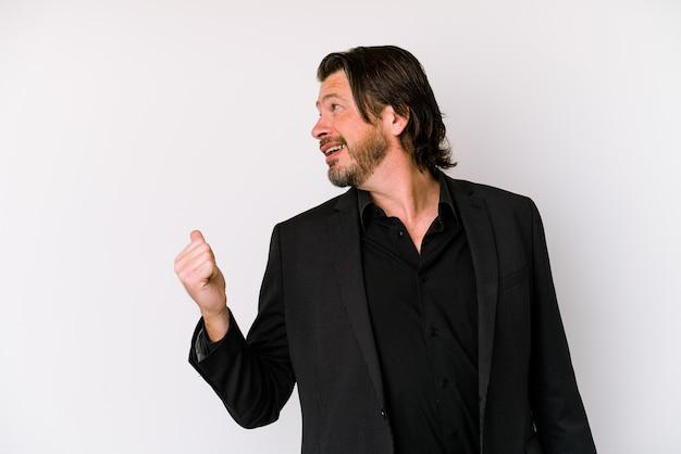 L'uomo olandese di affari di mezza età isolato su sfondo bianco punta con il pollice lontano, ridendo e spensierato.