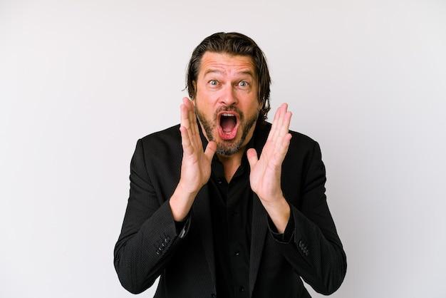 Uomo olandese d'affari di mezza età isolato su sfondo bianco grida forte, tiene gli occhi aperti e le mani tese.