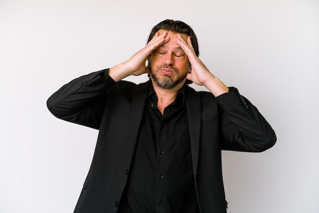 Uomo olandese di affari di mezza età isolato su sfondo bianco alza le spalle e gli occhi aperti confusi.