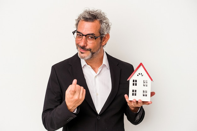 Uomo d'affari di mezza età che tiene fatture e modello di casa isolato su sfondo blu che punta con il dito su di te come se invitasse ad avvicinarsi.