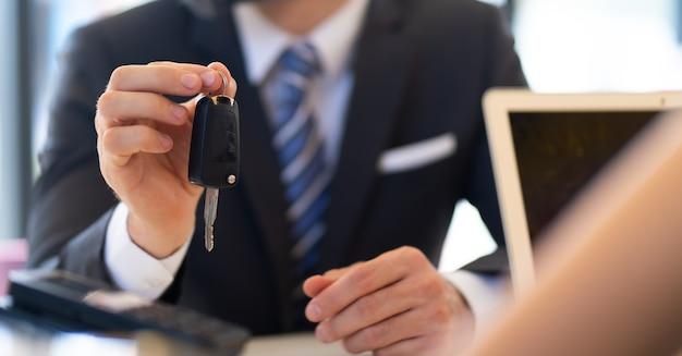 L'uomo d'affari di mezza età con la barba dà la chiave dell'auto al servizio clienti presso la stazione di manutenzione dell'auto e il garage di servizio automobilistico
