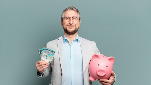 Uomo d'affari di mezza età con soldi e un salvadanaio