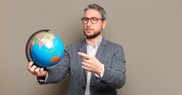 Uomo d'affari di mezza età con una mappa del globo del mondo