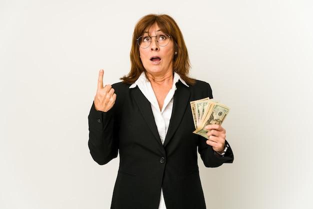 La mezza età caucasica donna d'affari in possesso di banconote isolato rivolto verso l'alto con la bocca aperta.