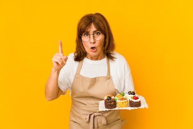 Donna caucasica del cuoco di mezza età che ha un'idea, concetto di ispirazione.