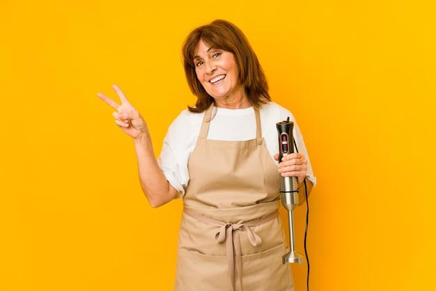 Donna caucasica del cuoco di mezza età che tiene un mixer isolato gioioso e spensierato che mostra un simbolo di pace con le dita.