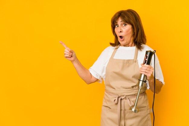 Donna caucasica del cuoco di mezza età che tiene un miscelatore isolato che indica al lato