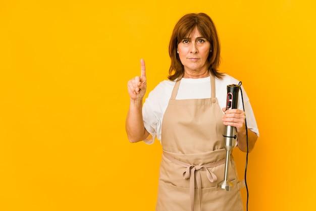 Donna caucasica del cuoco di mezza età che tiene un miscelatore isolato che mostra il numero uno con il dito.