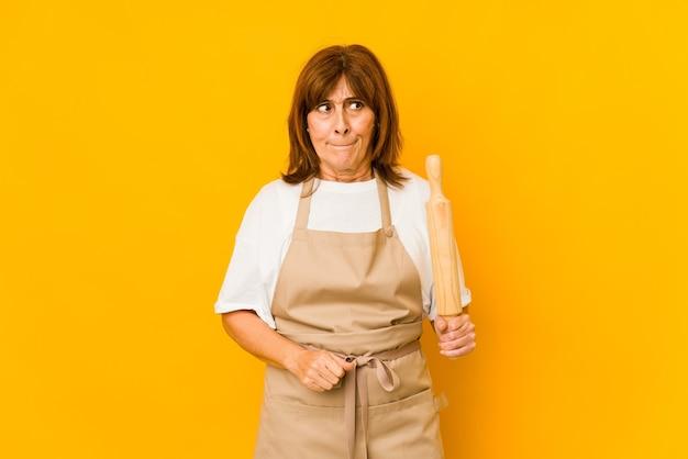 La donna caucasica del cuoco di mezza età che tiene un rullo isolato confusa, si sente dubbiosa e insicura.