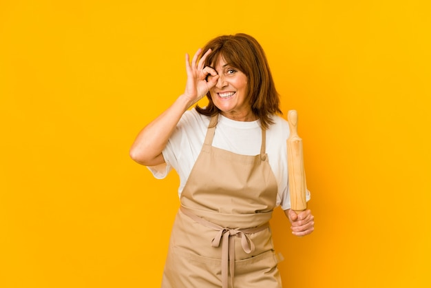 La donna caucasica del cuoco di mezza età che tiene un rullo ha isolato eccitato mantenendo il gesto giusto sull'occhio.