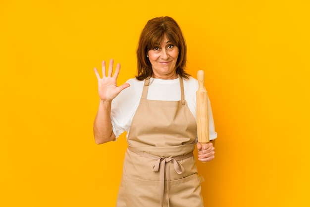 Donna caucasica del cuoco di mezza età che tiene un rullo isolato sorridente allegro che mostra il numero cinque con le dita.