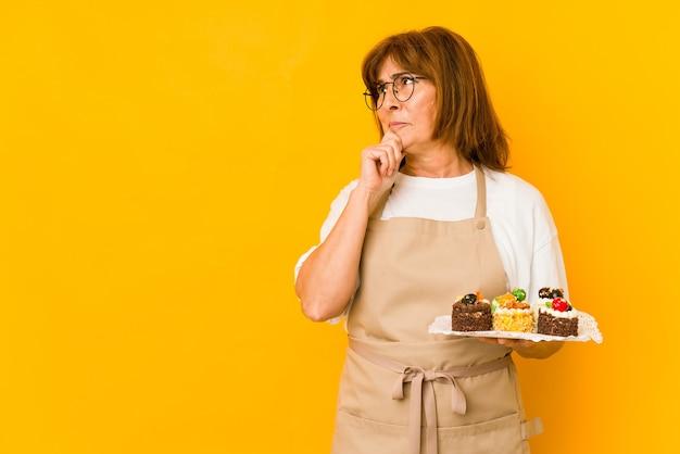 Donna caucasica del cuoco di mezza età che osserva obliquamente con espressione dubbiosa e scettica.