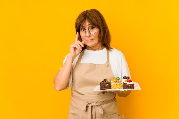 La donna caucasica del cuoco di mezza età che indica il tempiale con il dito, pensando, si è concentrata su un compito.