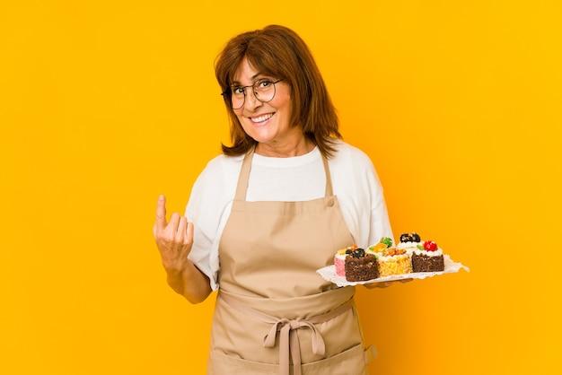 Donna caucasica del cuoco di mezza età che indica con il dito contro di voi come se invitando ad avvicinarsi.