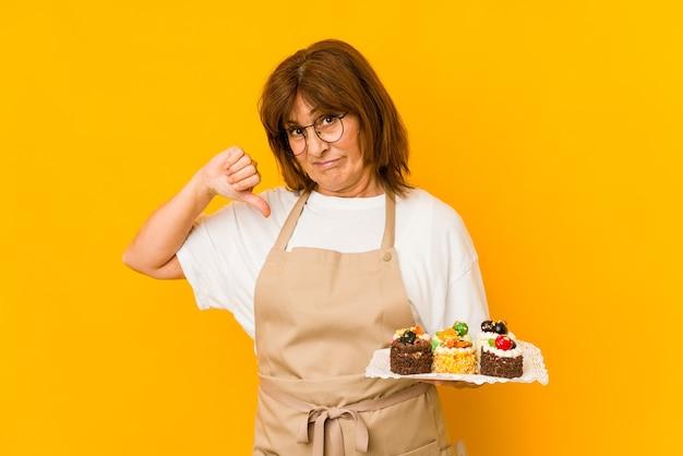 Donna caucasica del cuoco di mezza età che mostra un gesto di antipatia, i pollici giù. concetto di disaccordo.
