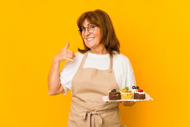 Donna caucasica del cuoco di mezza età che mostra un gesto di chiamata di telefono cellulare con le dita.