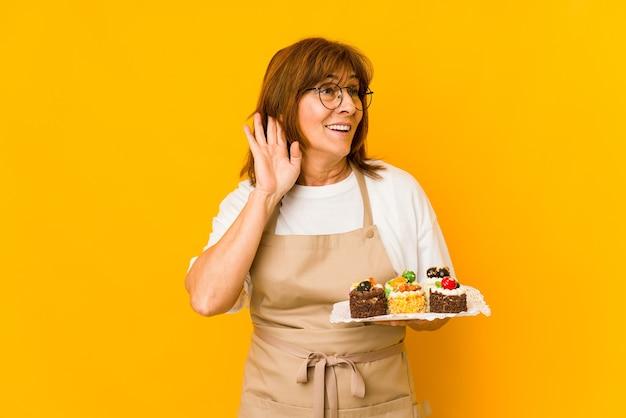 Donna caucasica del cuoco di mezza età che prova ad ascoltare un pettegolezzo.