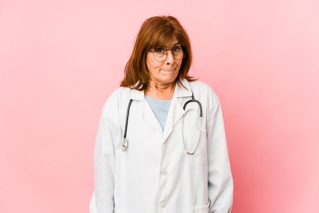 La donna caucasica del medico di mezza età isolata confusa, si sente dubbiosa e insicura.