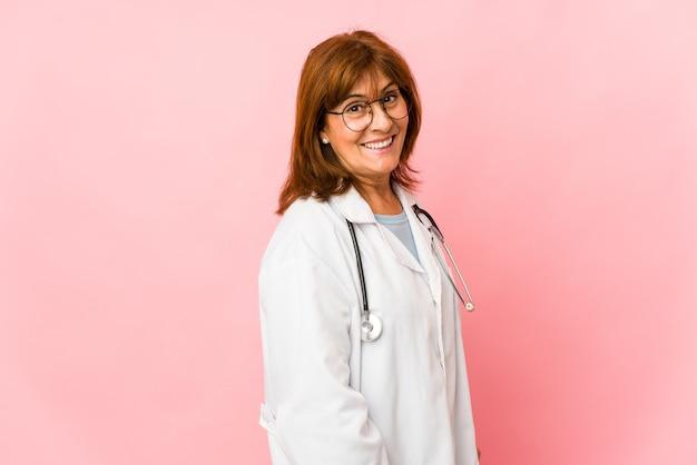 La donna caucasica di medico di mezza età isolata osserva da parte sorridente, allegra e piacevole.