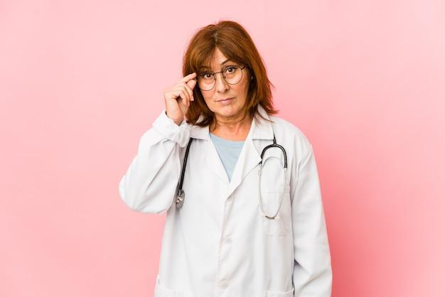 La mezza età caucasica medico donna isolato tempio puntato con il dito, pensando, concentrato su un compito.